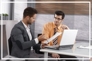 Businessmen discussing finance at desk, working together, using laptop computer-729081-edited.jpg