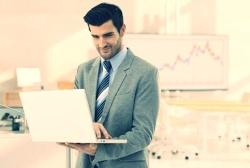 Online degree in UAE Businessman working with laptop in meeting room, smiling-100660-edited.jpg