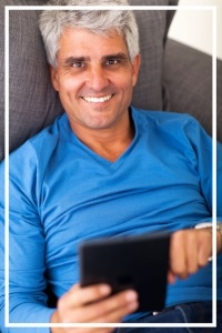 Overhead portrait of mature man using tablet computer while lying on sofa-673564-edited.jpg