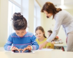 education, elementary school, technology and children concept - little student girl with tablet pc over classroom and teacher background-674336-edited.jpg