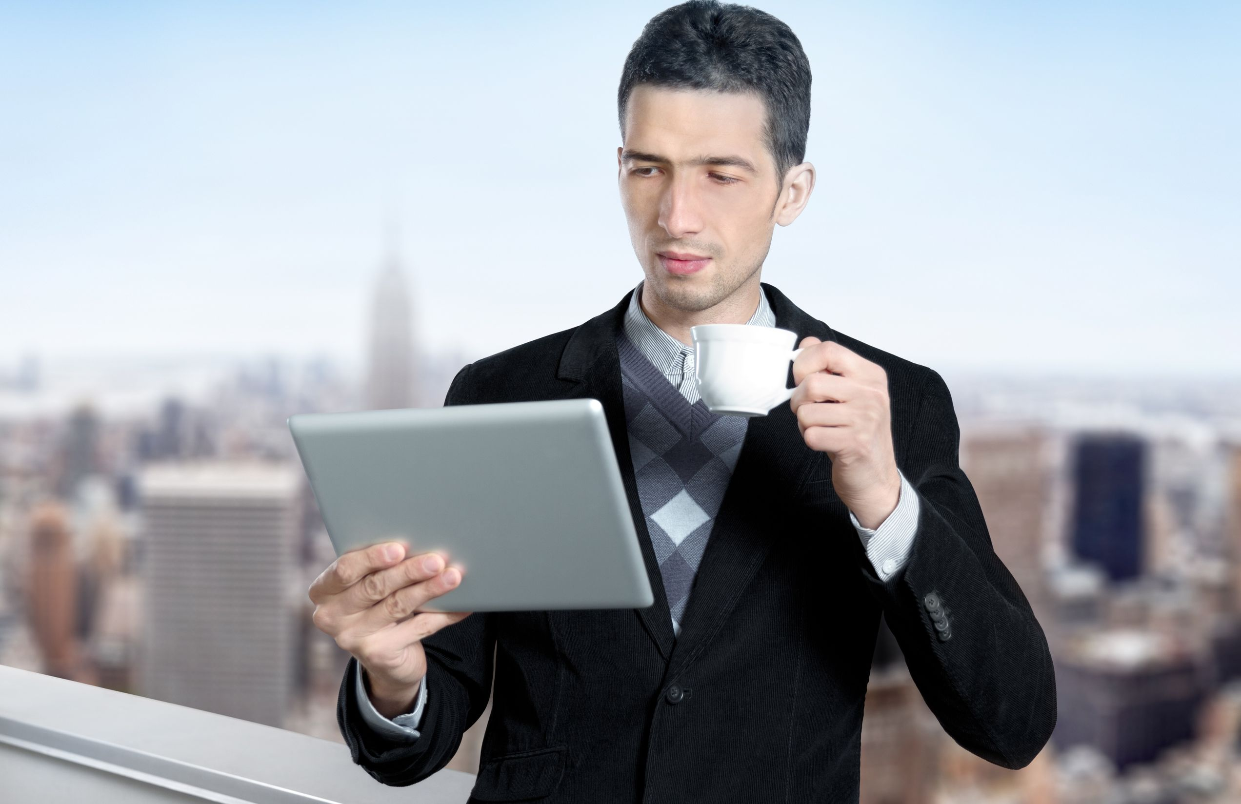 Young_businessman_with_a_cup_of_coffee_uses_a_digital_tablet.jpg